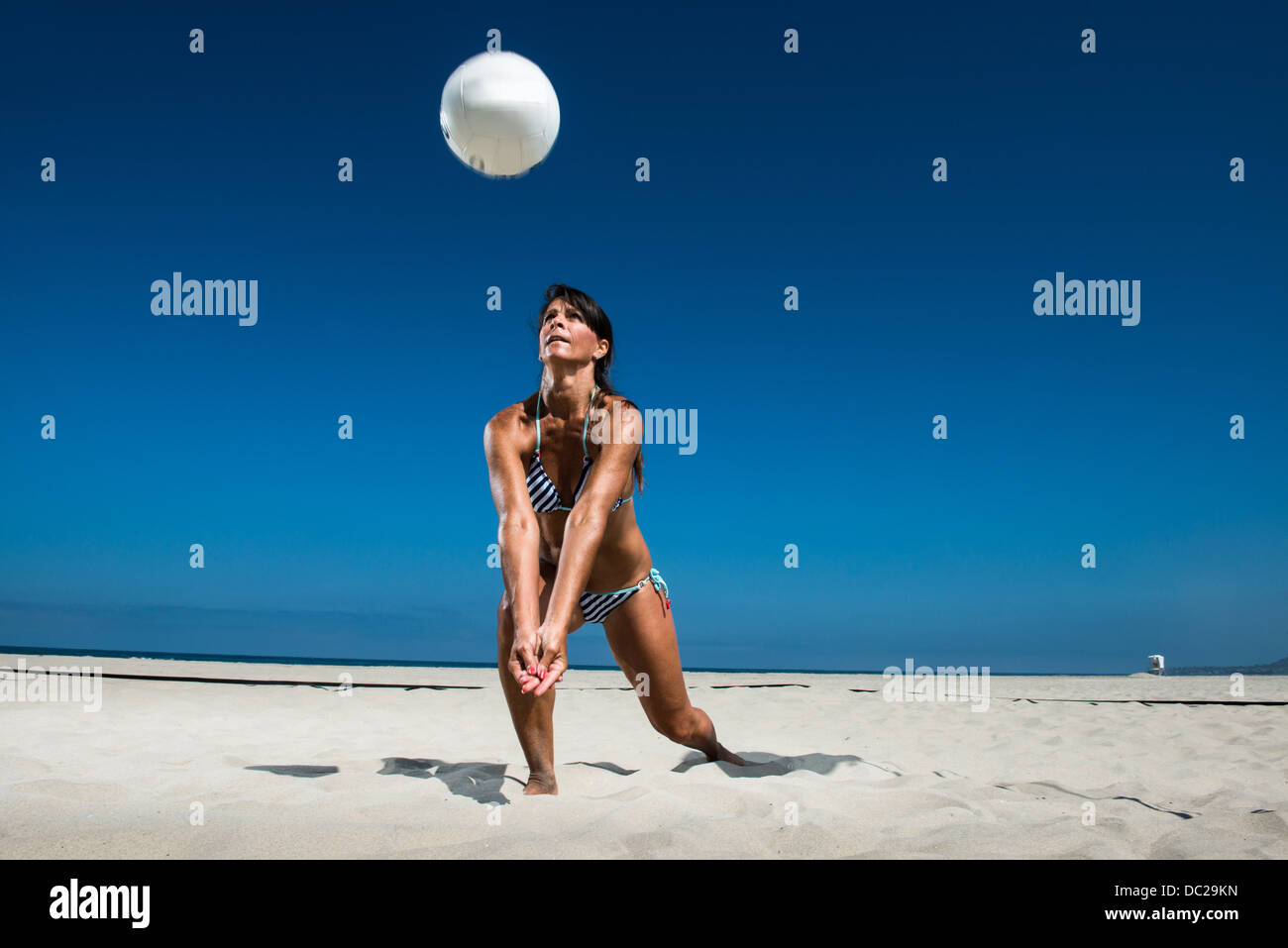Female beach volleyball player digging ball - Stock Image
