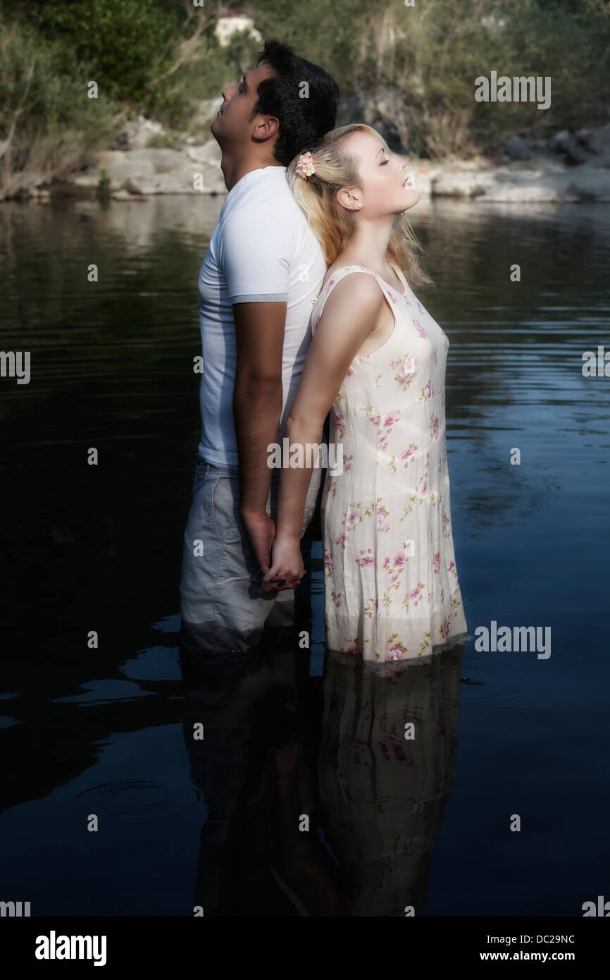 a couple in water, back to back - Stock Image