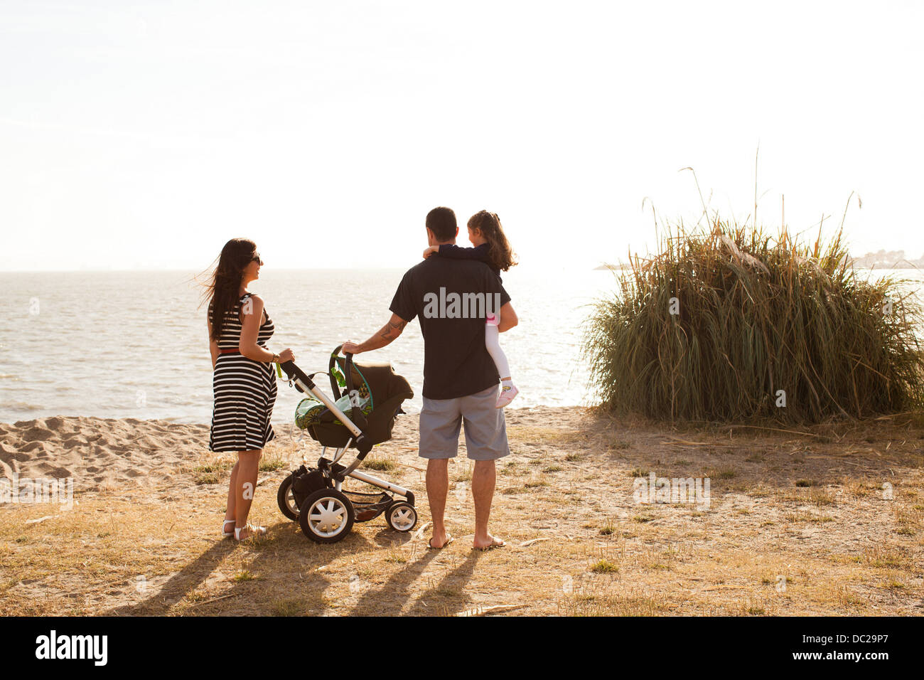 Family standing on beach looking at sea - Stock Image
