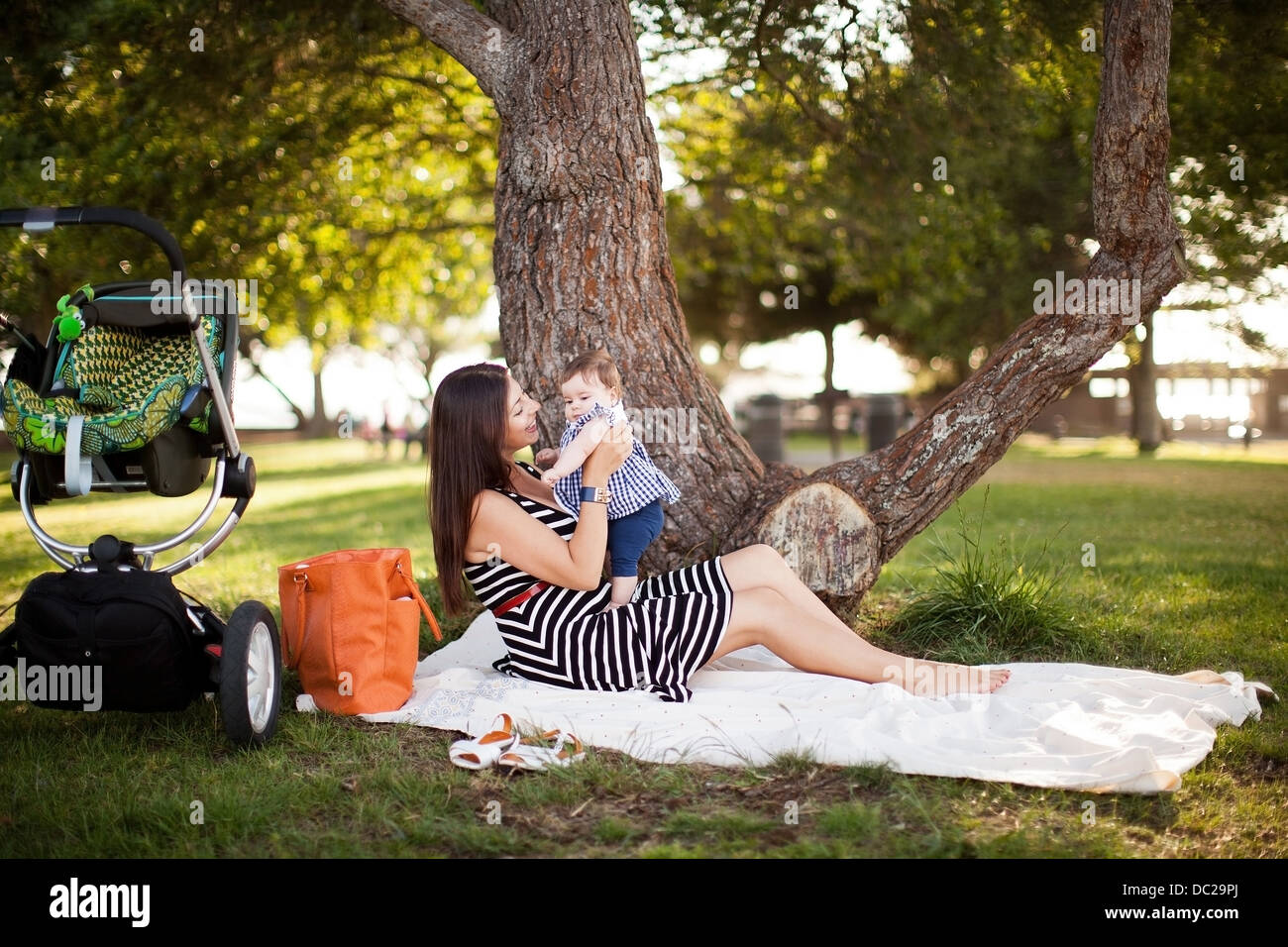 Mother sitting on picnic blanket with baby daughter - Stock Image