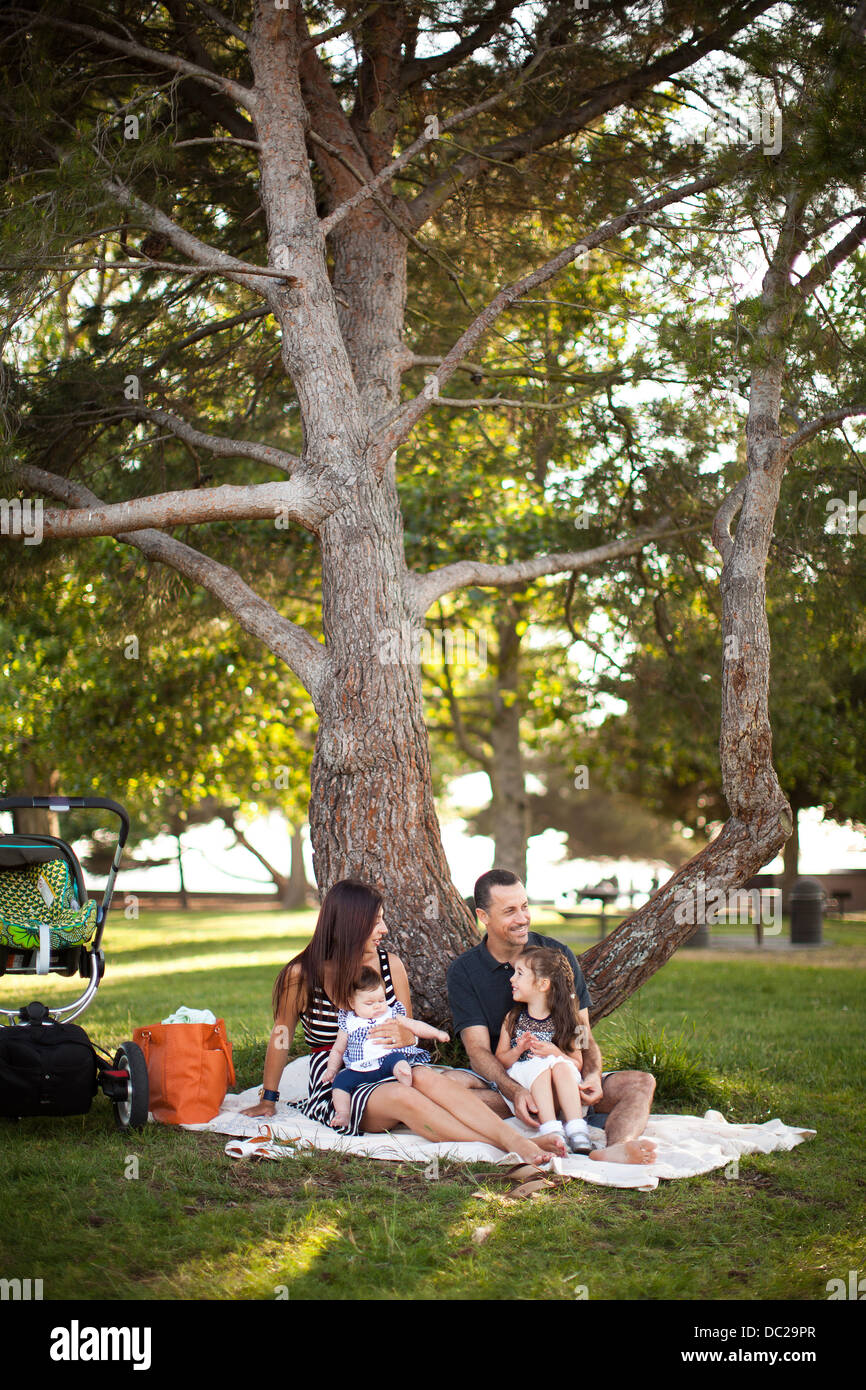 Family with two children sitting on picnic blanket under tree - Stock Image