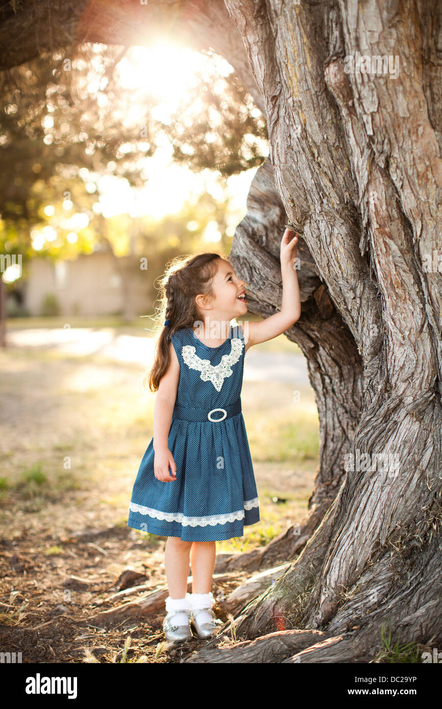 Portrait of girl touching tree trunk - Stock Image