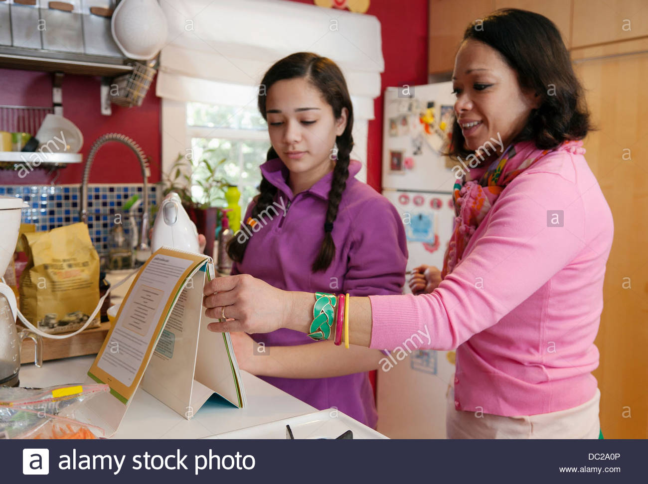Mother and daughter reading recipe - Stock Image