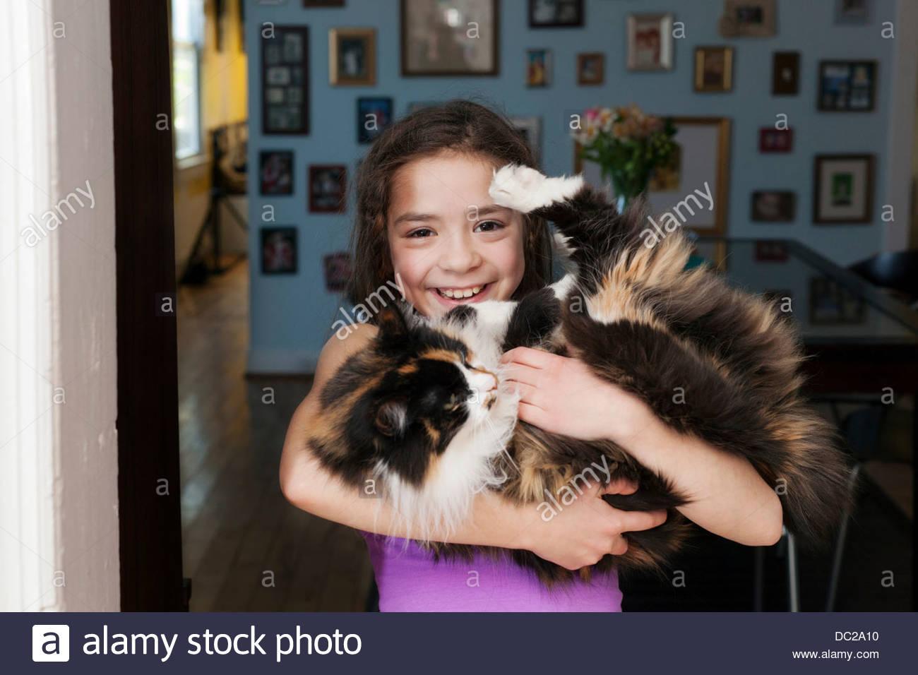 Girl holding pet cat - Stock Image