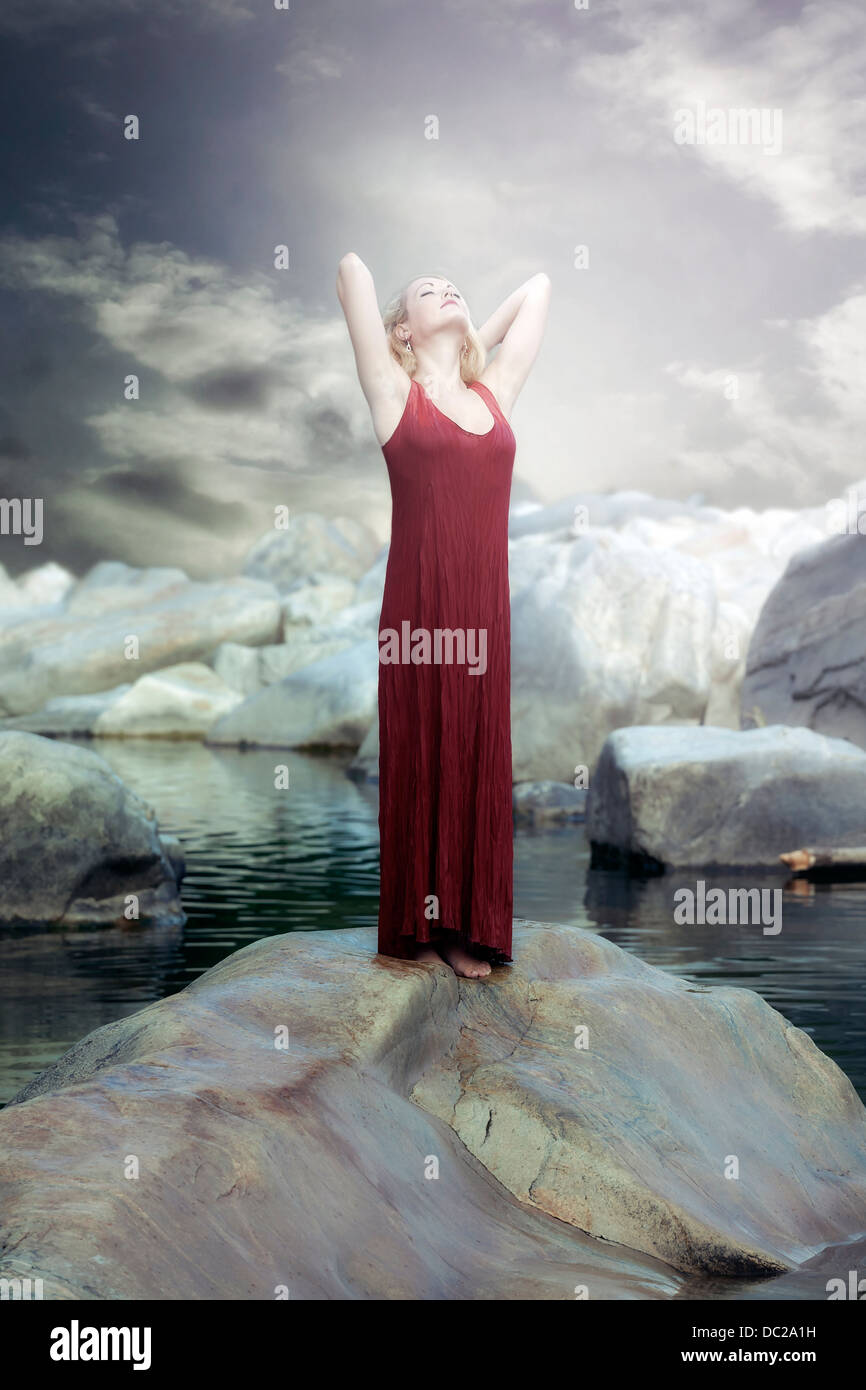 a woman in a red dress is standing on a rock in the water and enjoying the sun - Stock Image