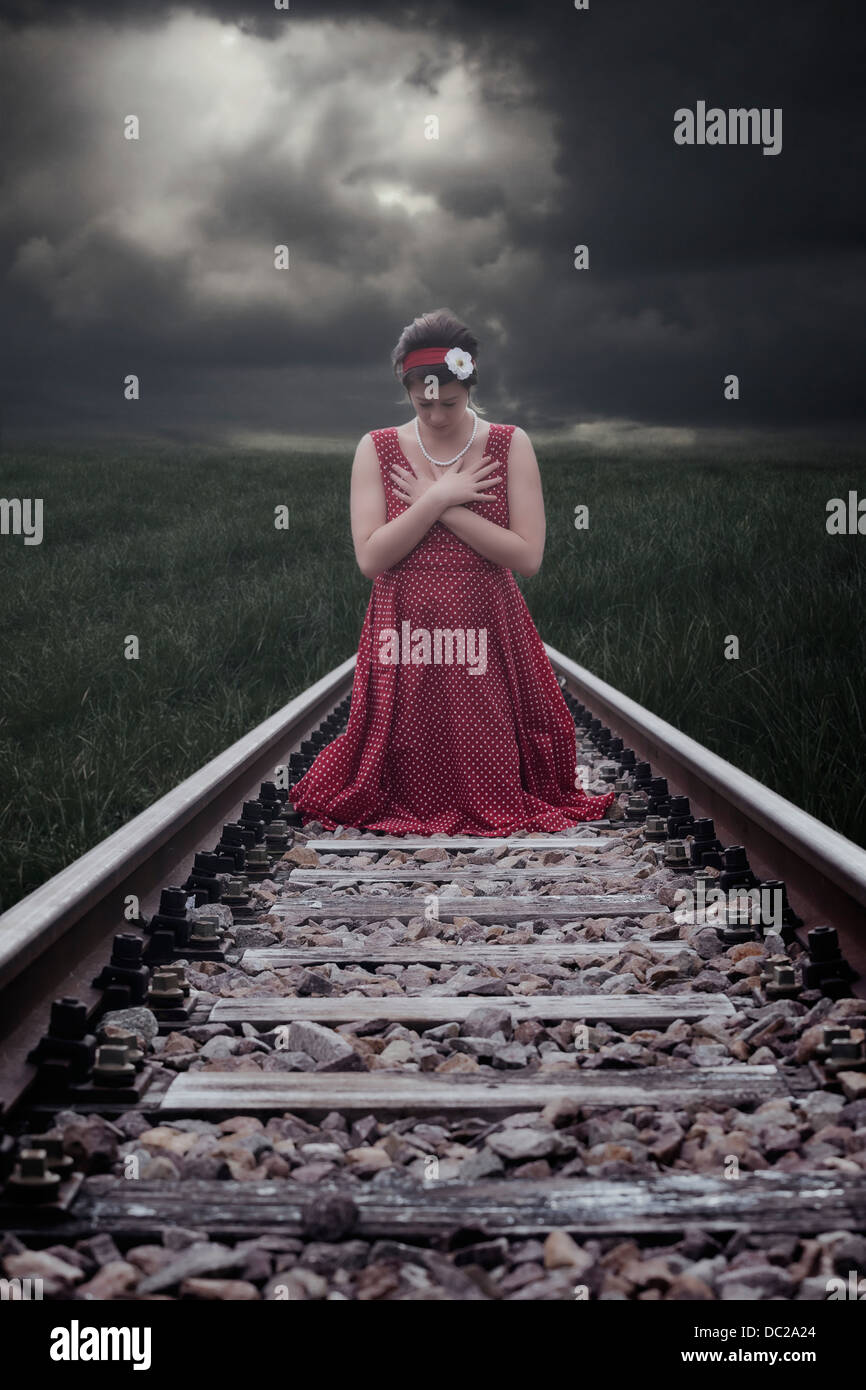 a girl in a red dress is sitting on railway tracks Stock Photo