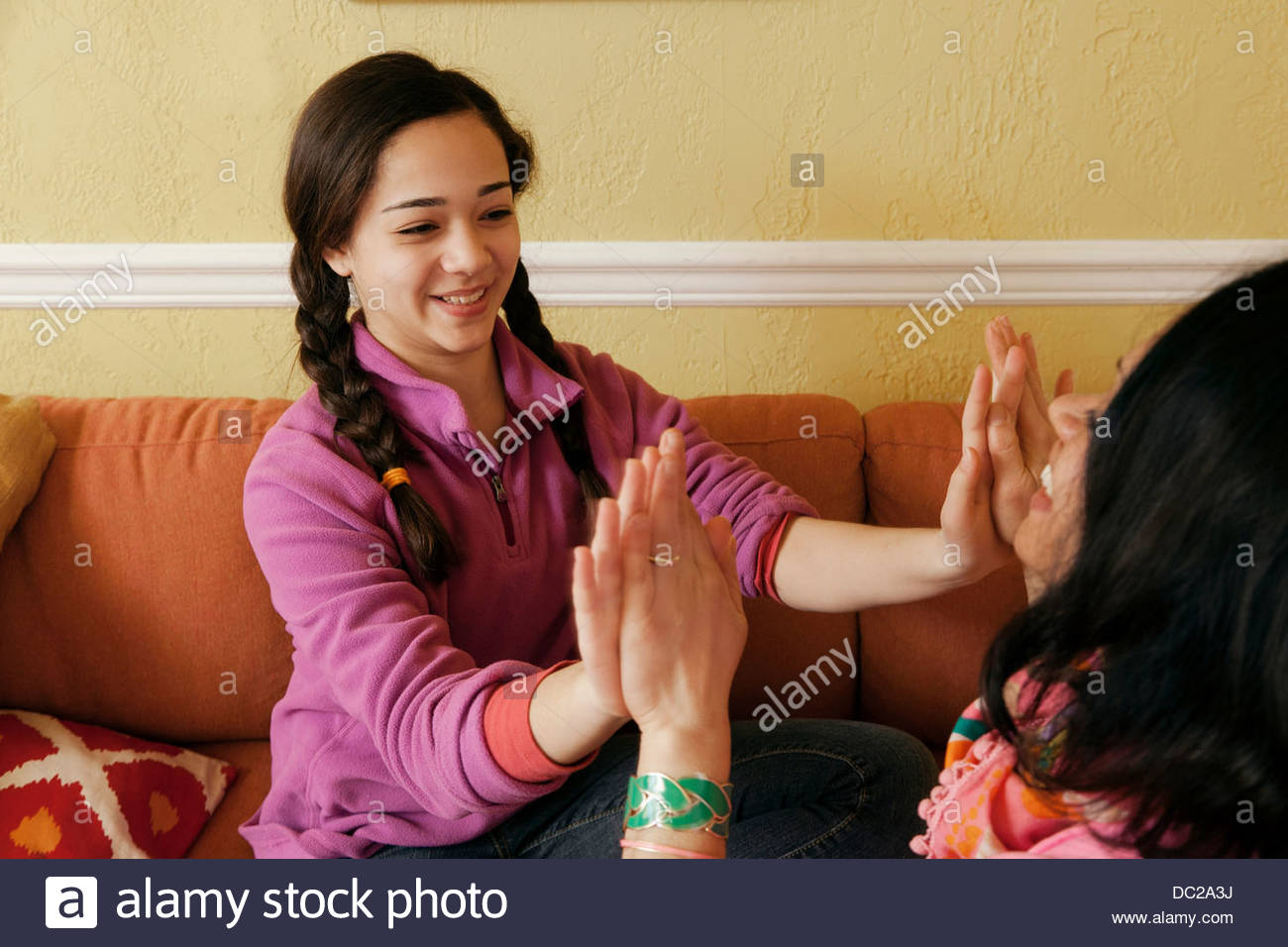 Teenage daughter playing pat a cake with mother - Stock Image