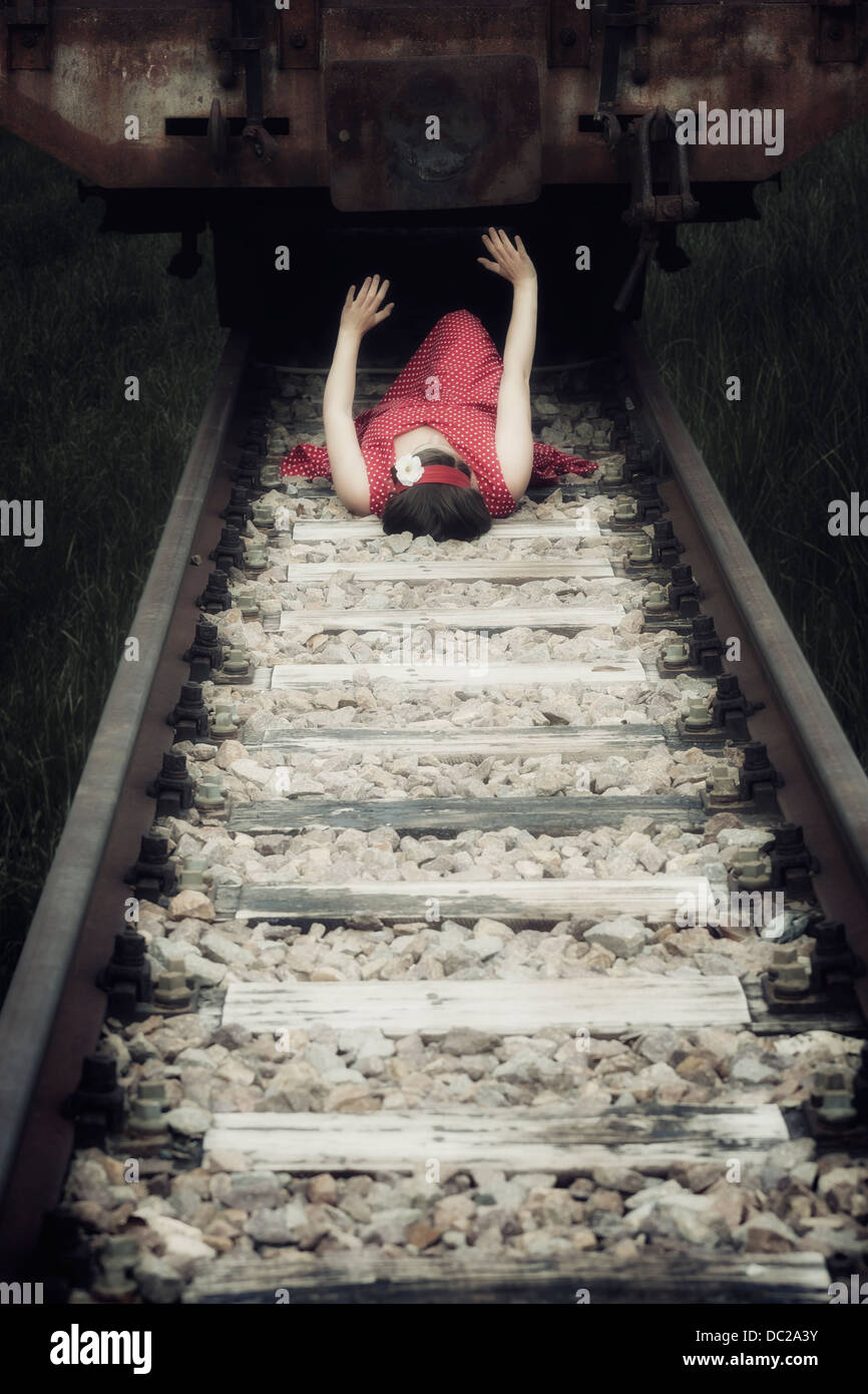 a girl in a red dress is lying under a wagon - Stock Image