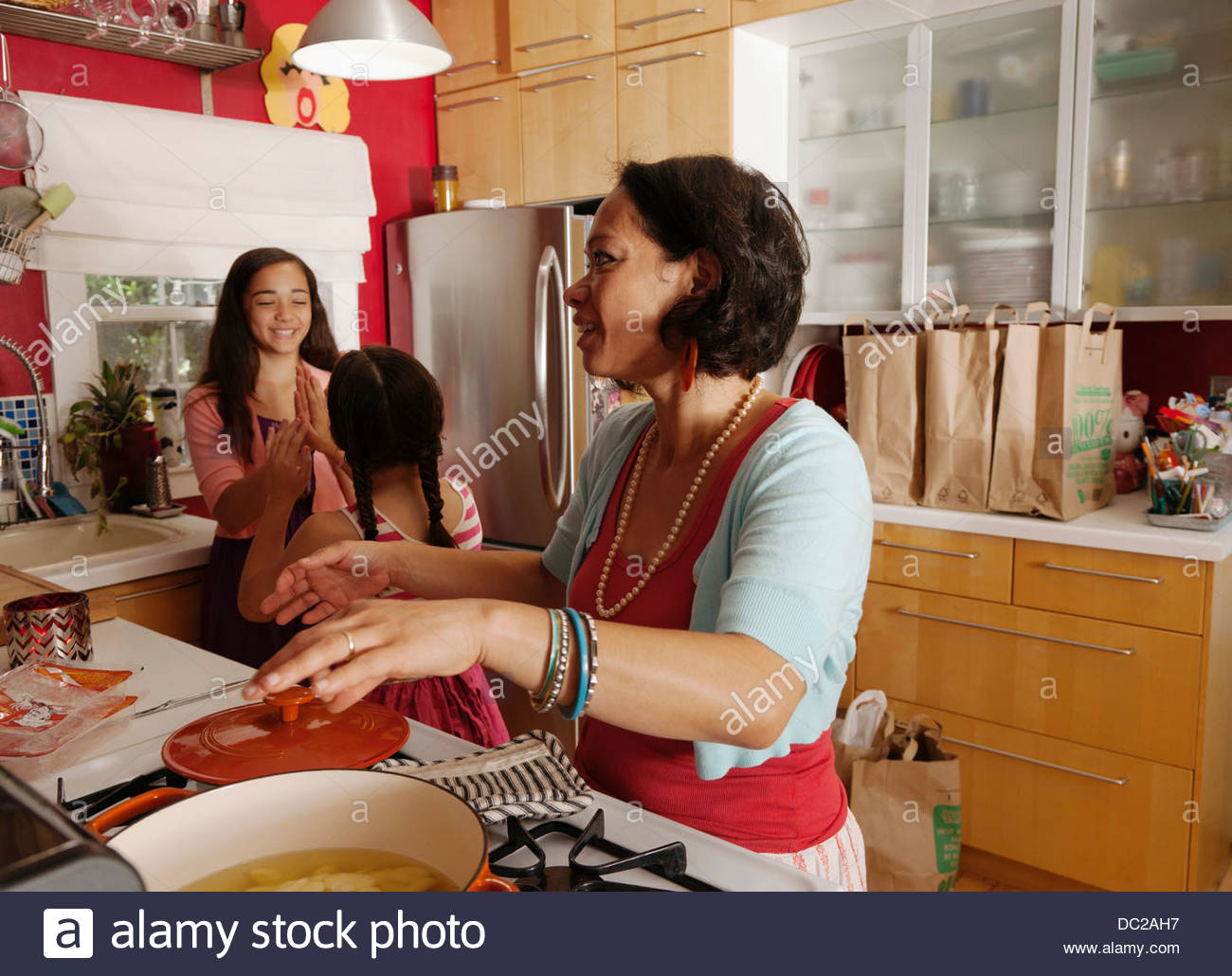 Mother and daughters in kitchen - Stock Image
