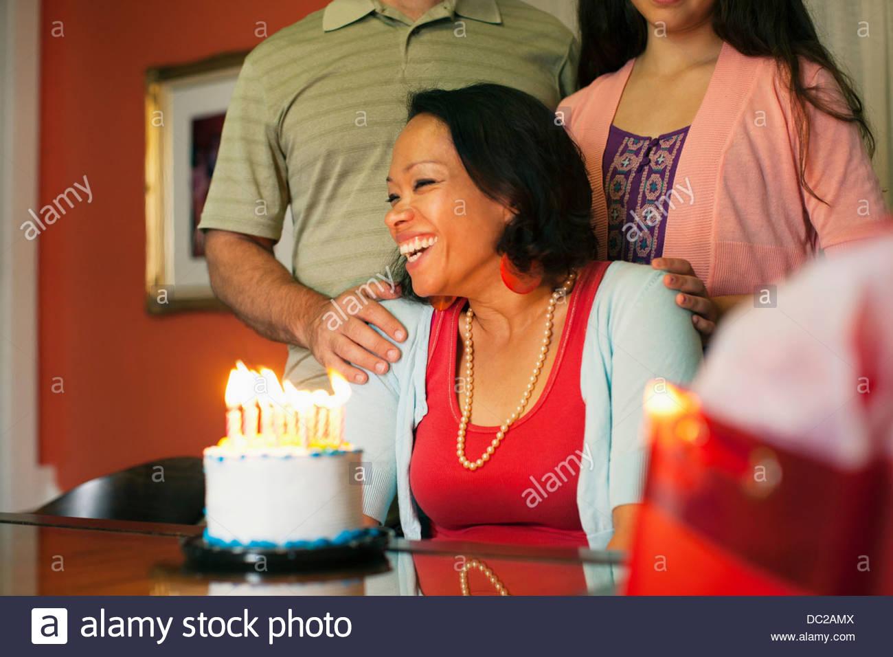 Woman smiling over birthday cake - Stock Image