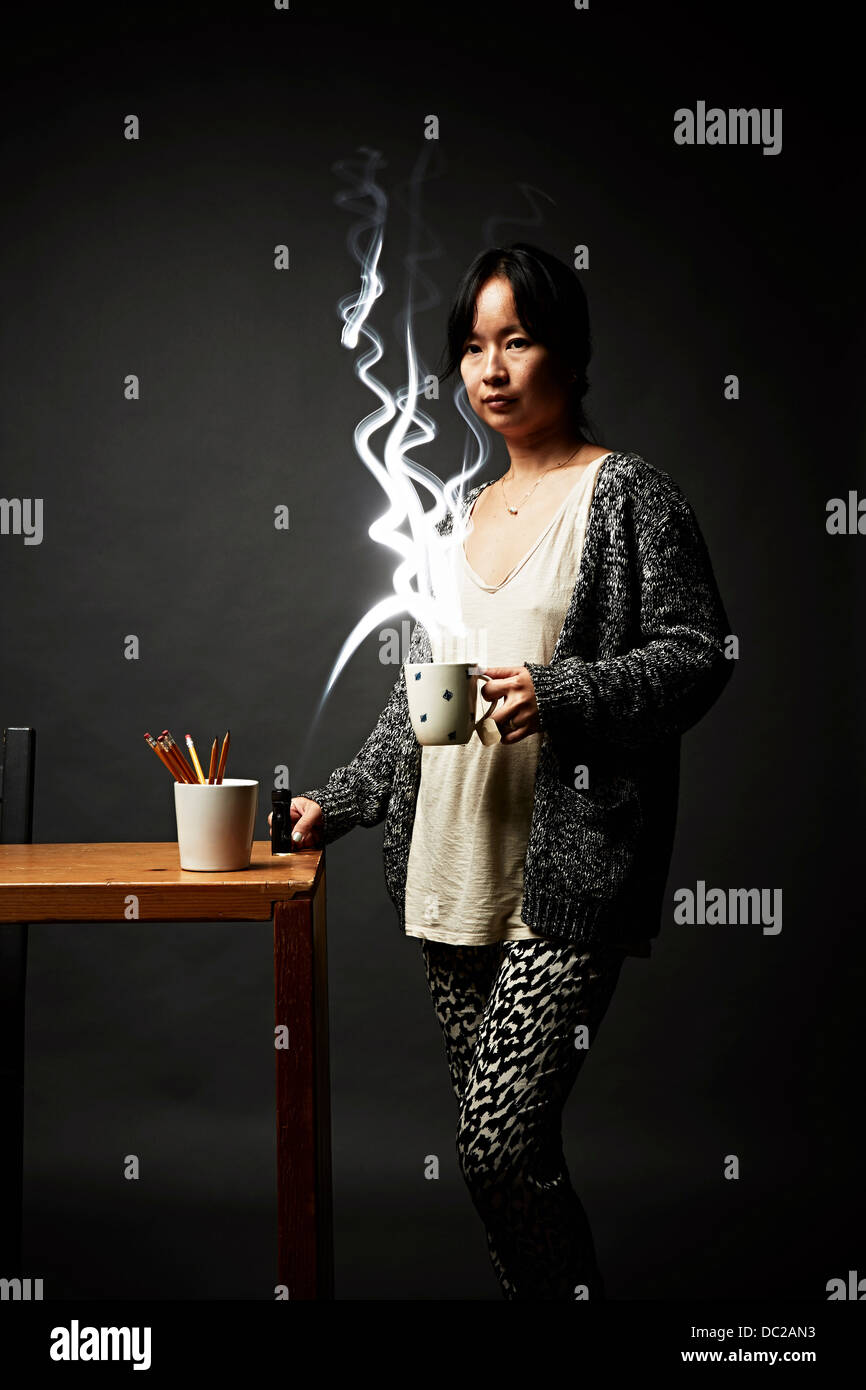 Woman holding mug contemplating - Stock Image