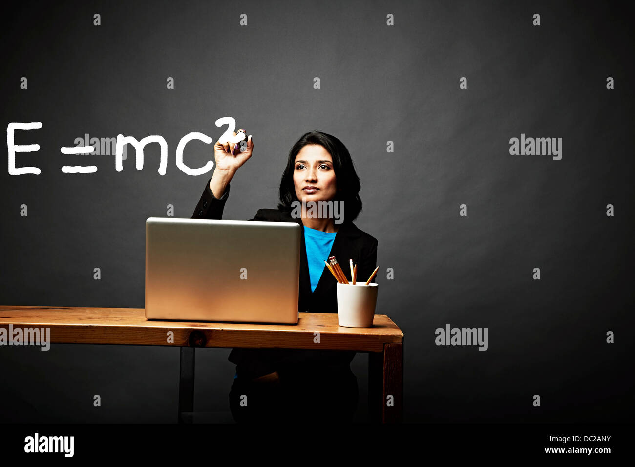 Woman solving a mathematical equation Stock Photo
