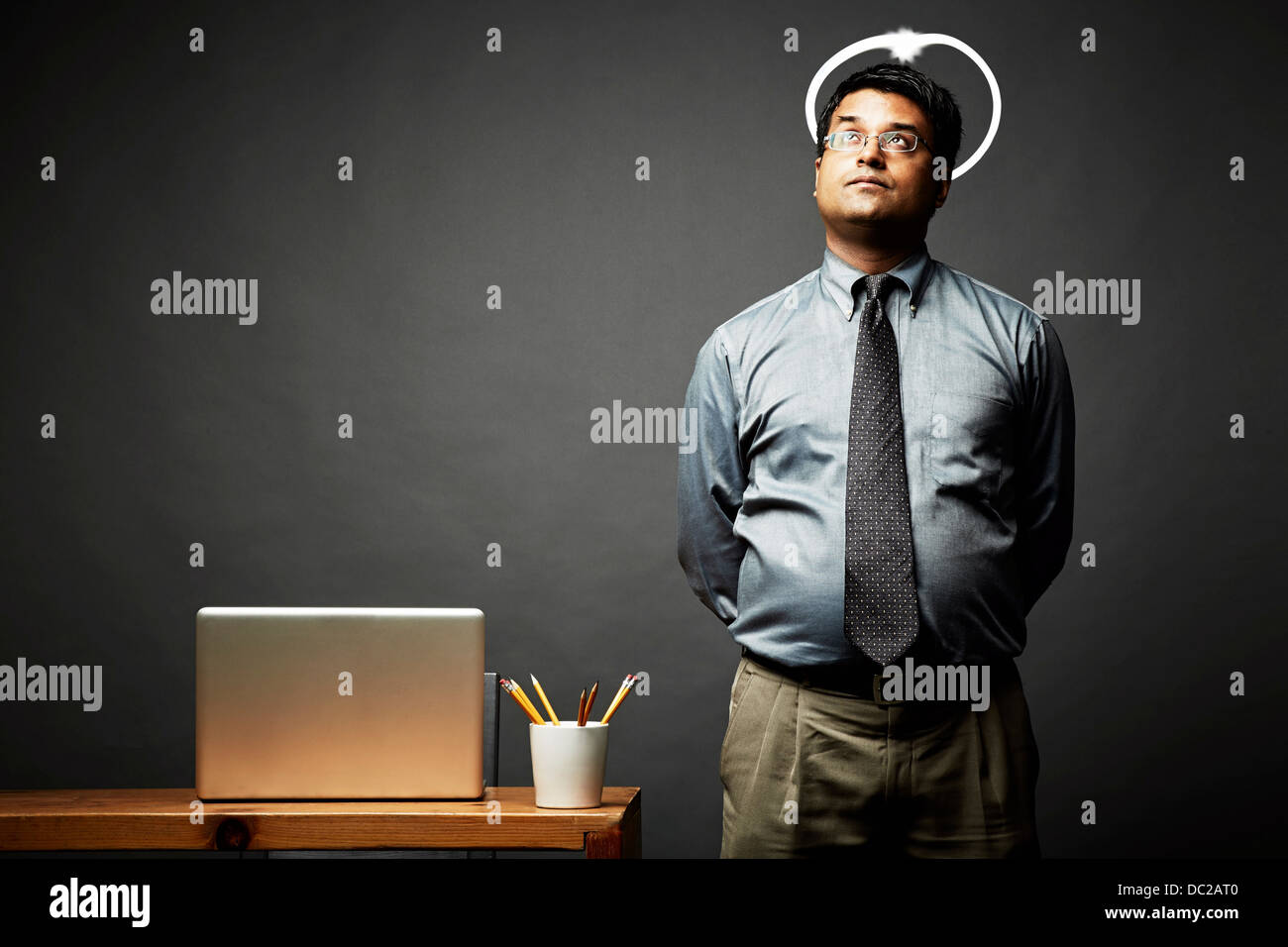 Man with hands behind back looking angelic - Stock Image