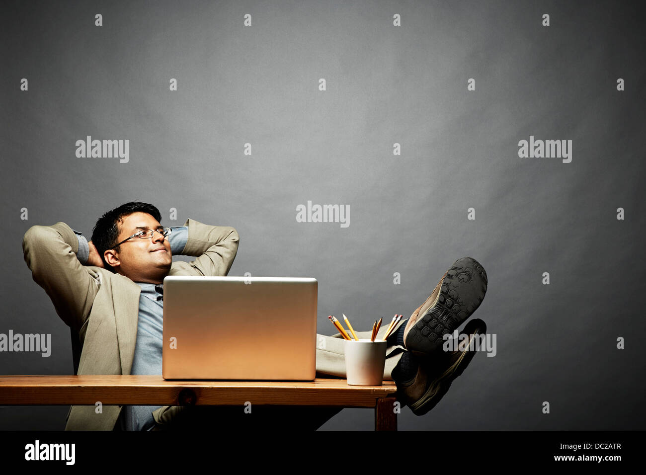 Man relaxing with feet up on table - Stock Image