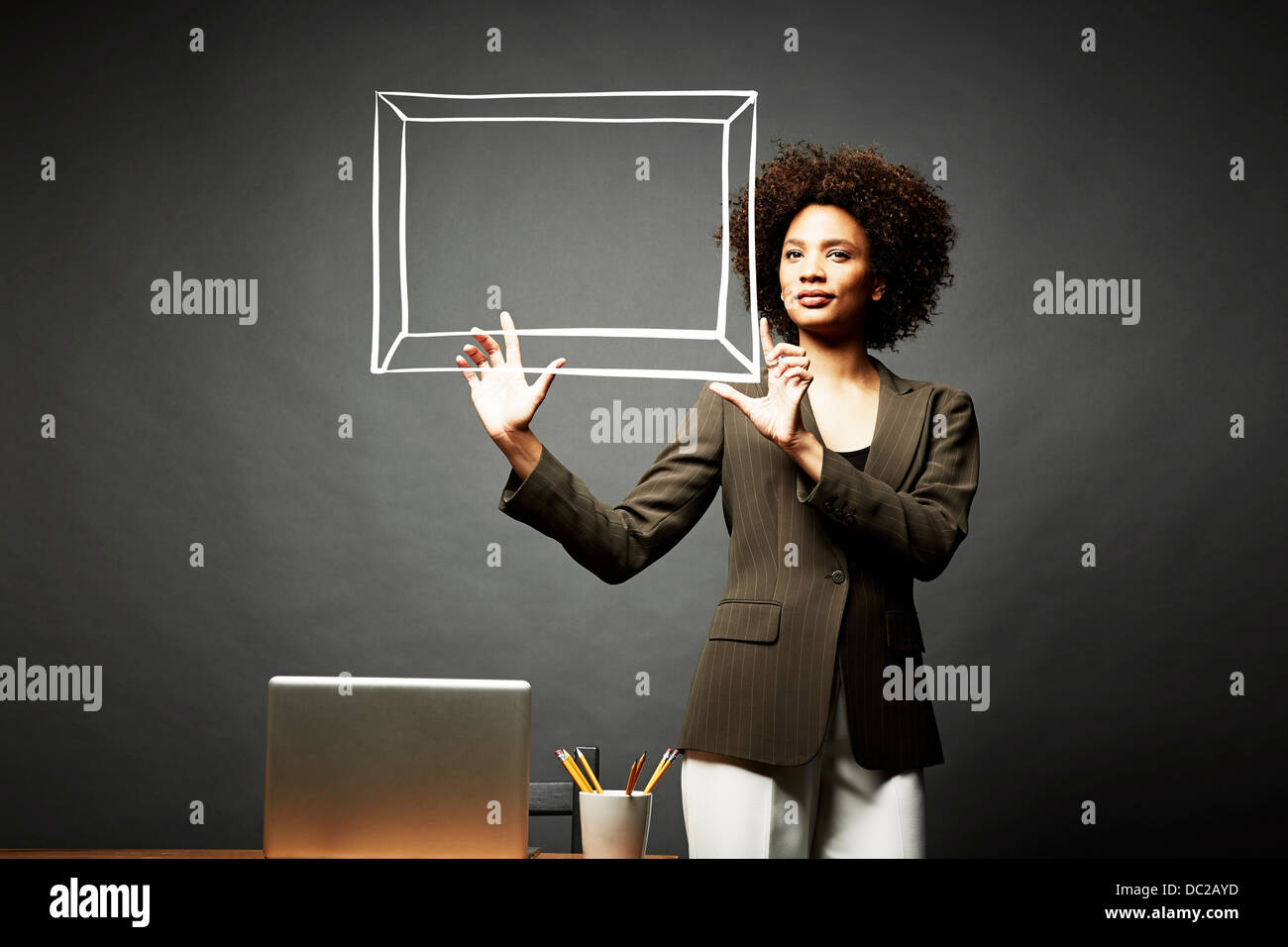 Woman holding up a picture frame - Stock Image