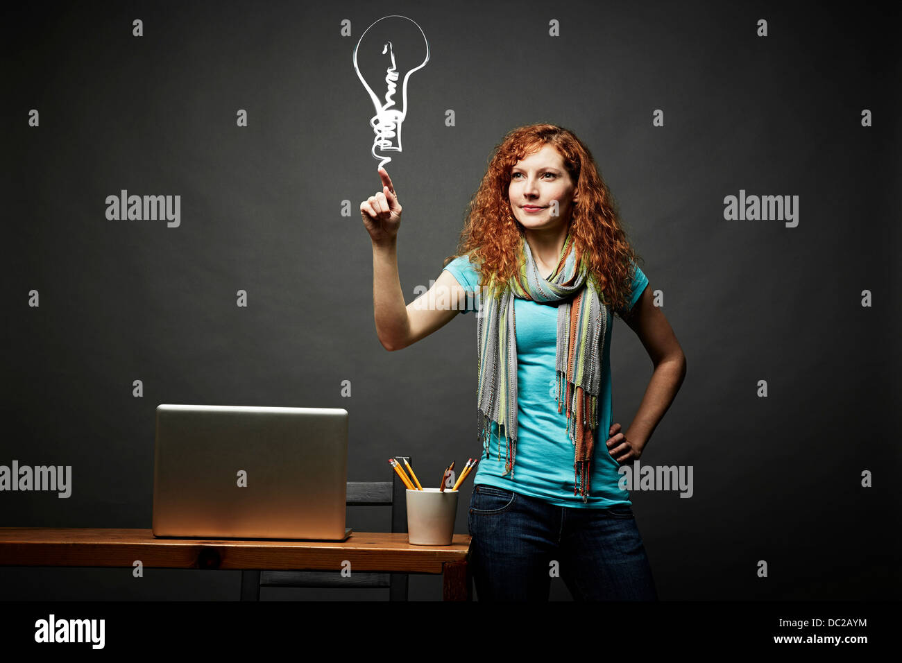 Woman drawing a light bulb - Stock Image