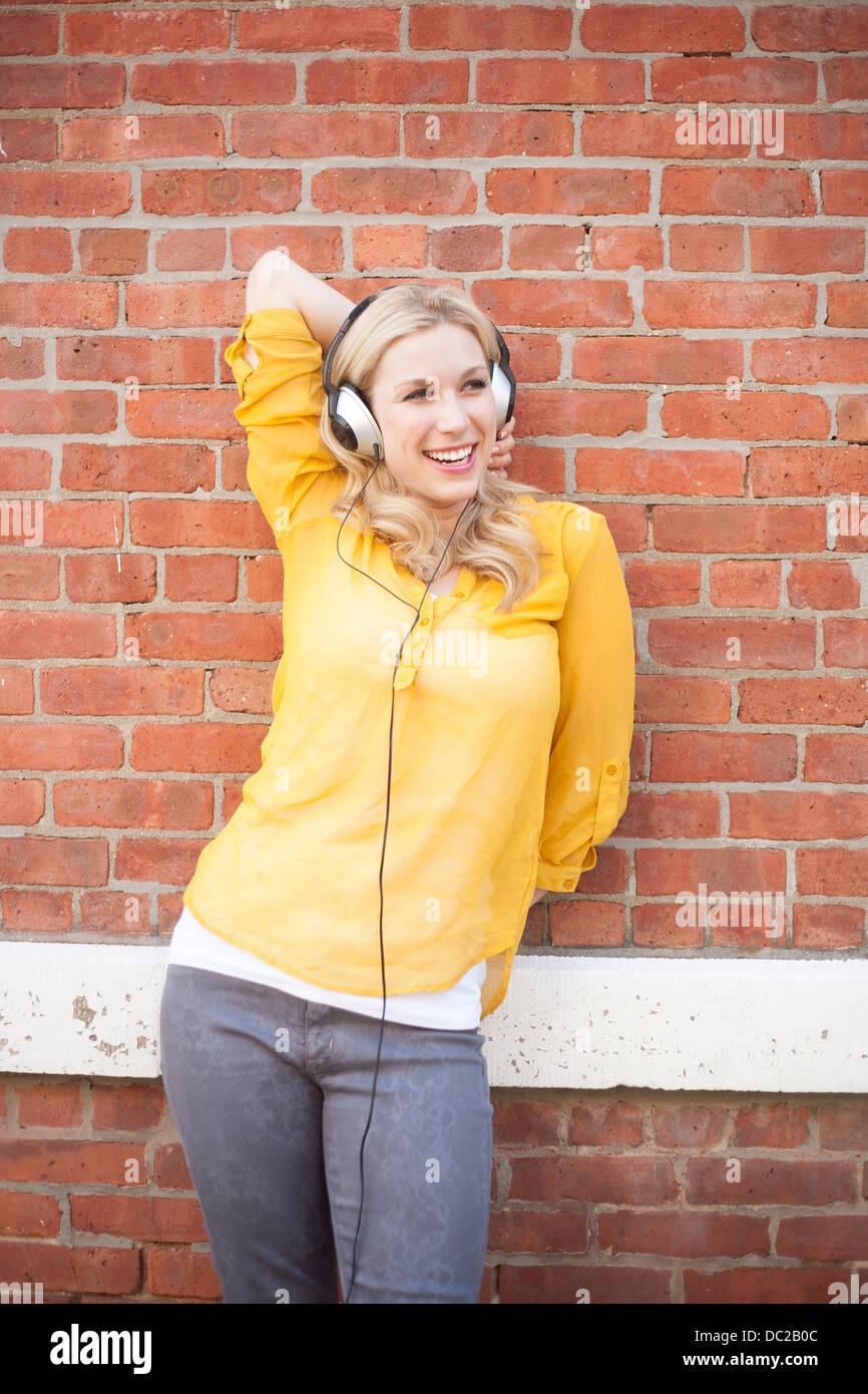 Woman wearing headphones standing against brickwall Stock Photo