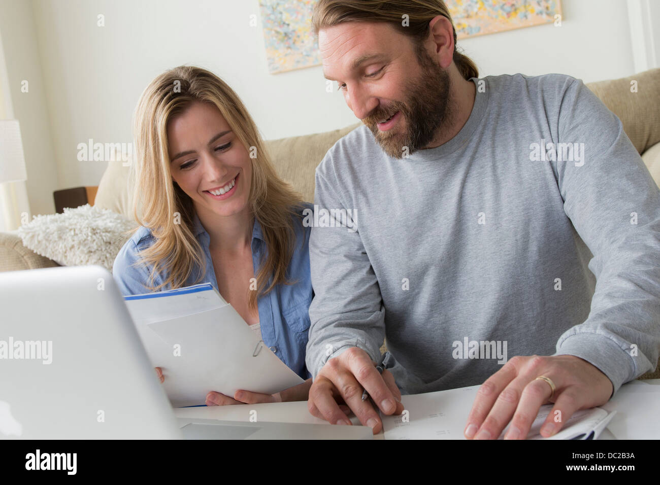 Husband and wife looking at letter - Stock Image