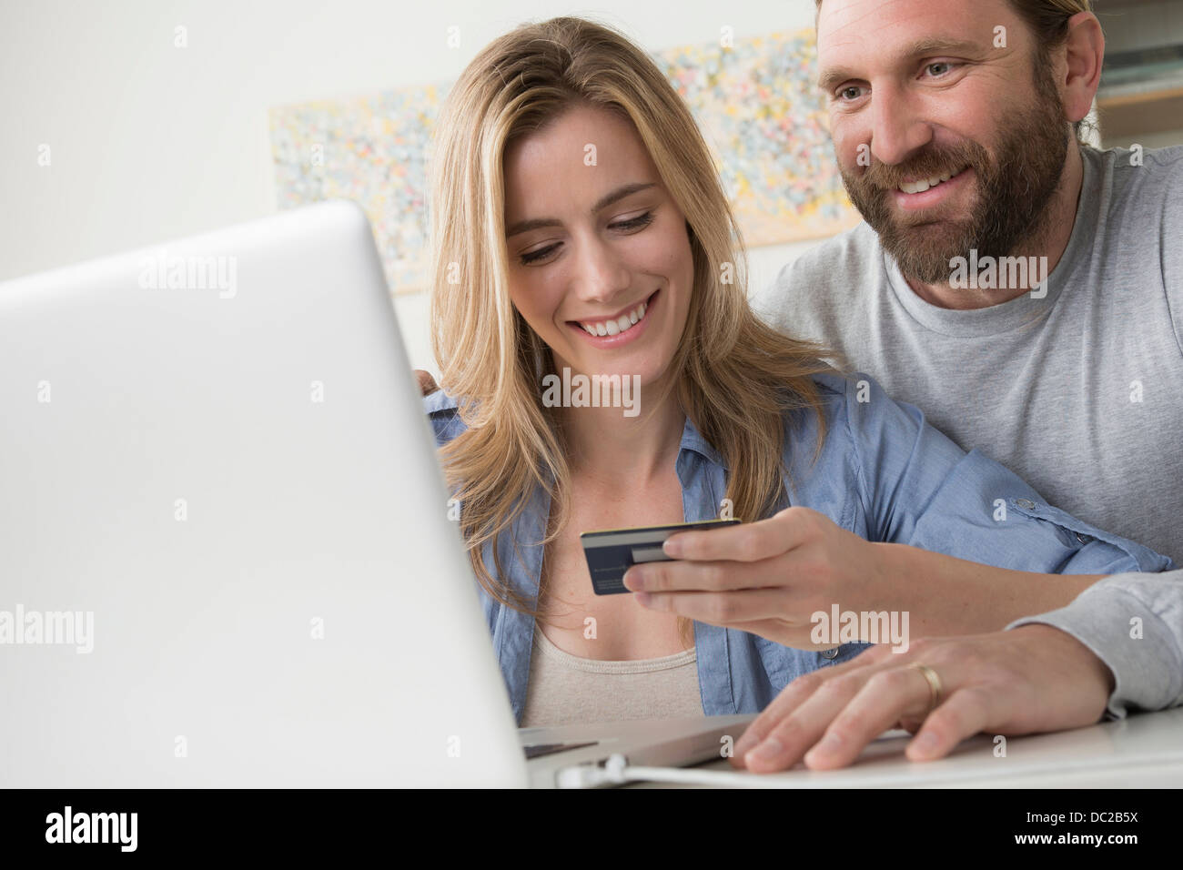 Husband with wife holding credit card Stock Photo