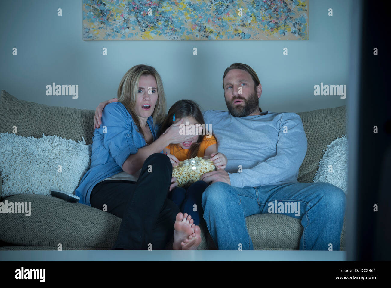 Parents and child watching horror movie - Stock Image