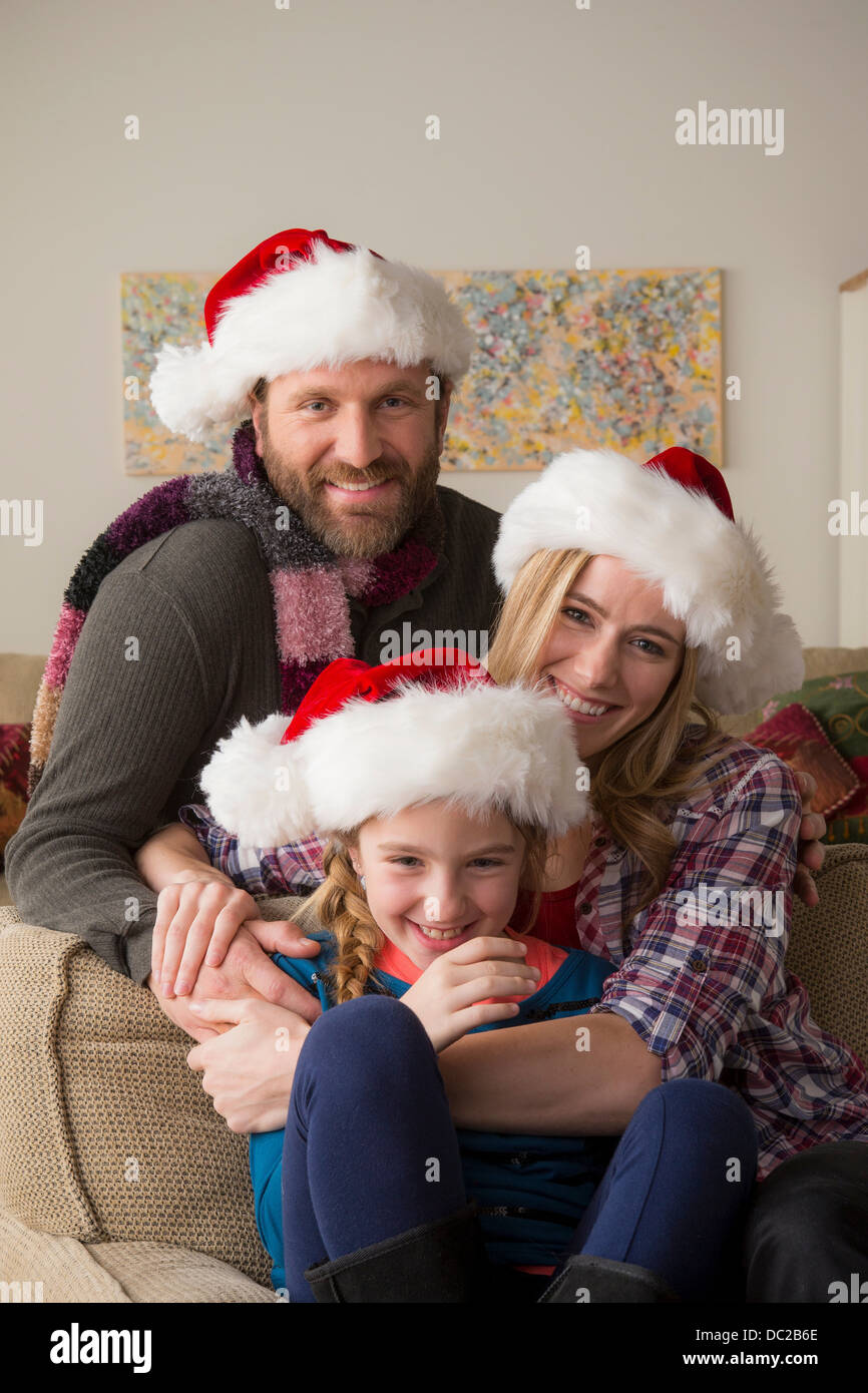 Parents and child in Santa hat posing for camera - Stock Image