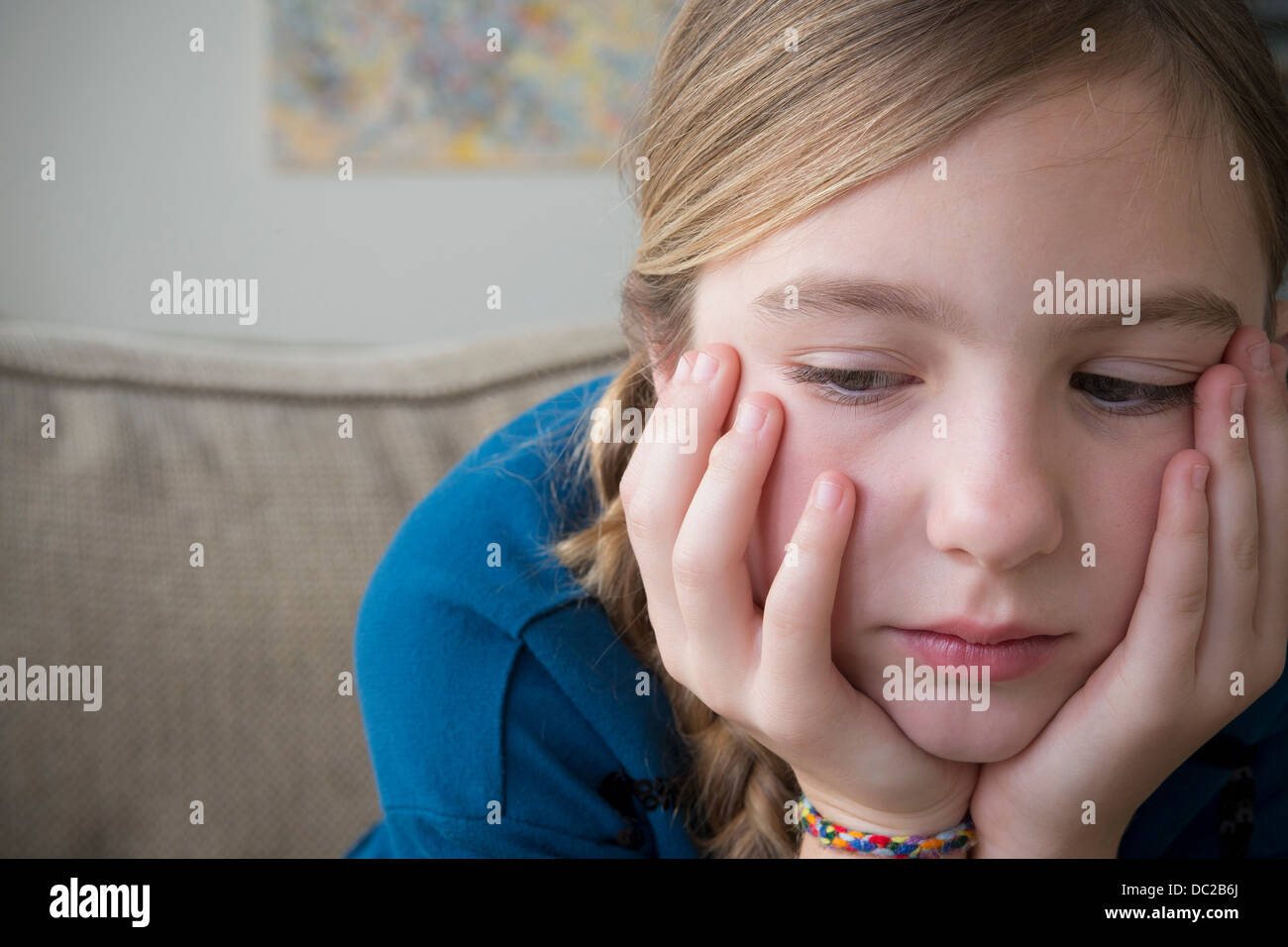 Girl with hands on face looking down - Stock Image