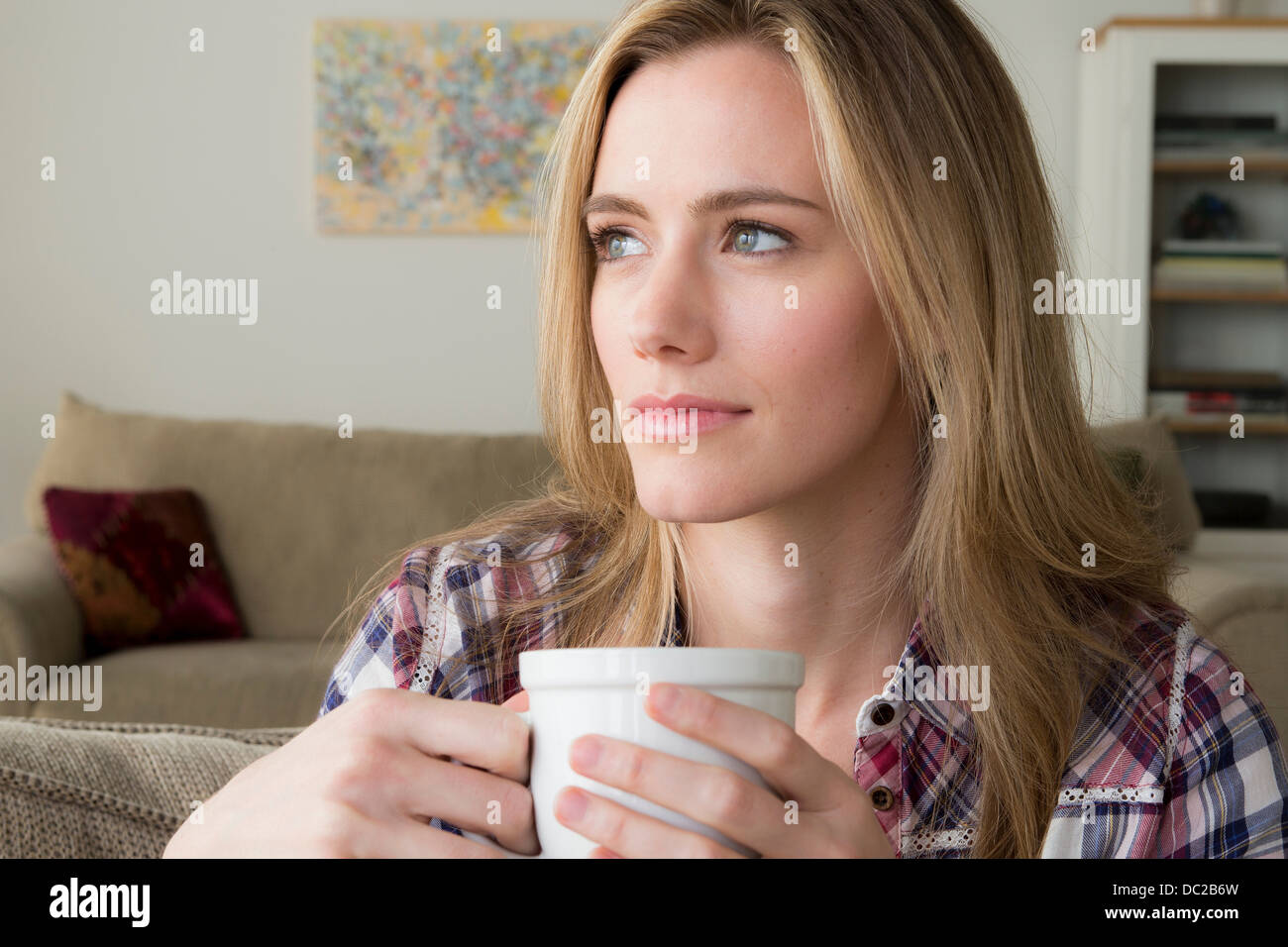 Woman with cup day dreaming - Stock Image