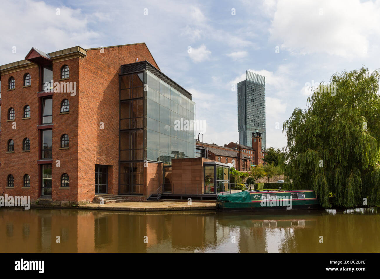 Bridgewater canal with narrow boat, redeveloped warehouse and Beetham Tower, Castlefield, Manchester. - Stock Image