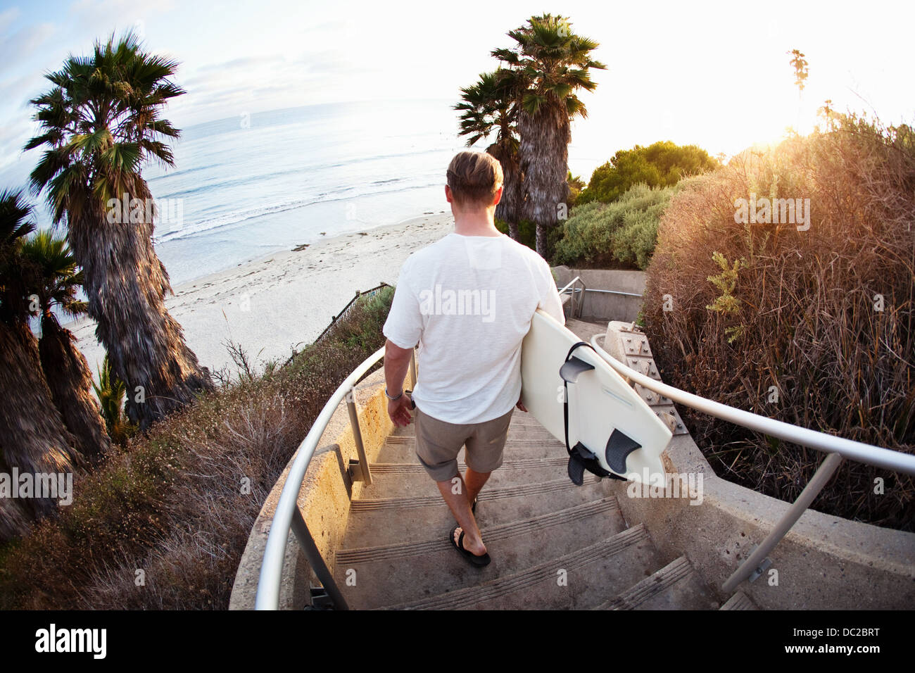 Surfer walking downstairs to beach - Stock Image