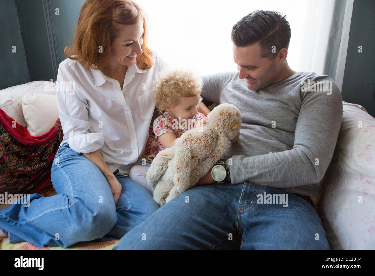 Husband & wife entertaining child - Stock Image