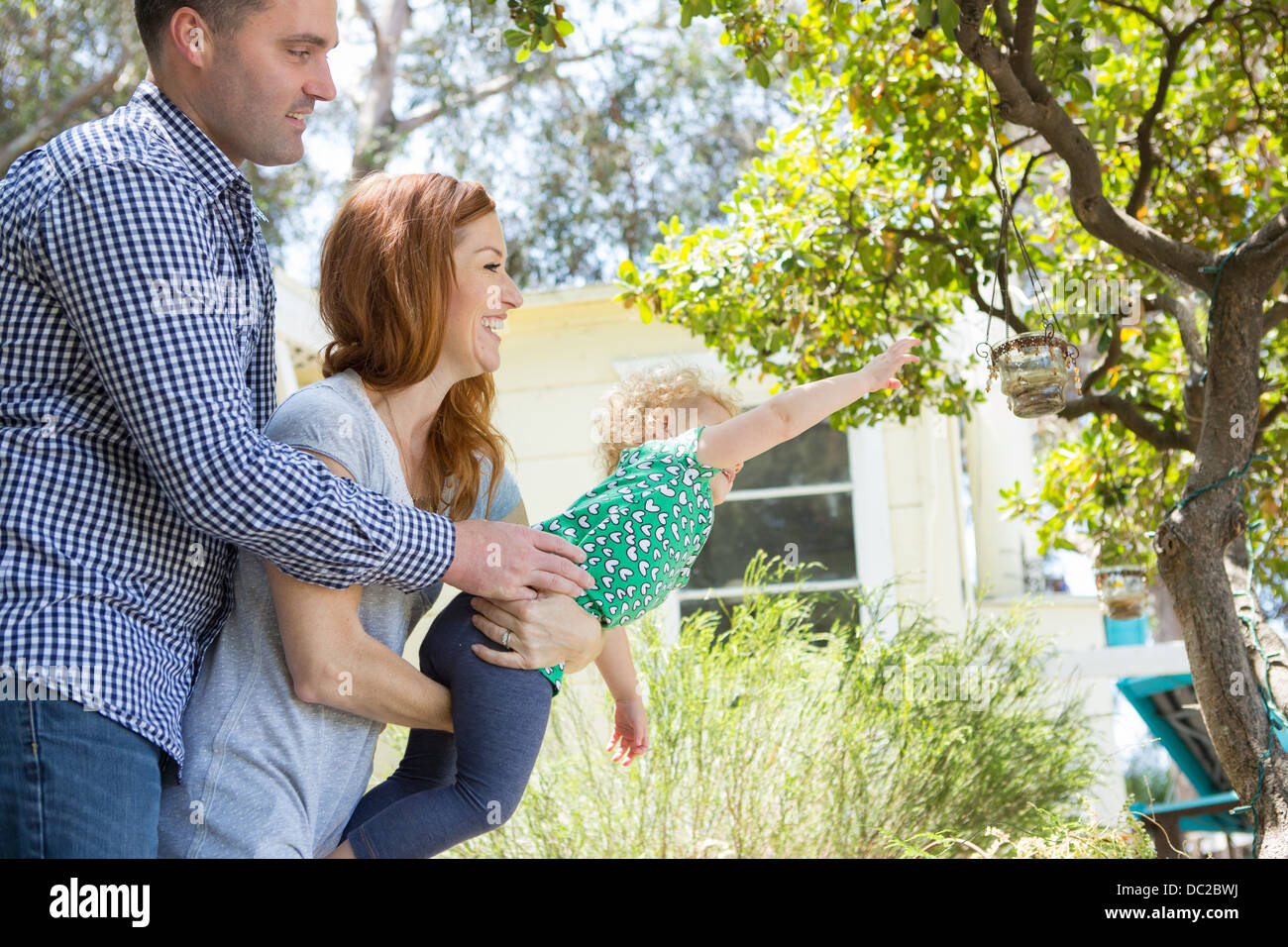 Couple carrying child reaching out - Stock Image