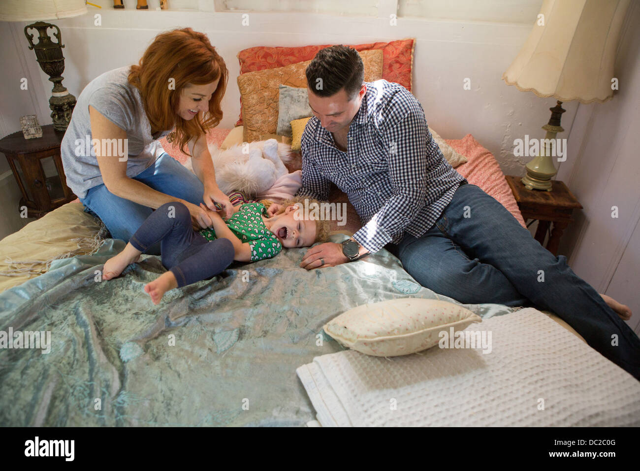 Husband and wife playing with child - Stock Image