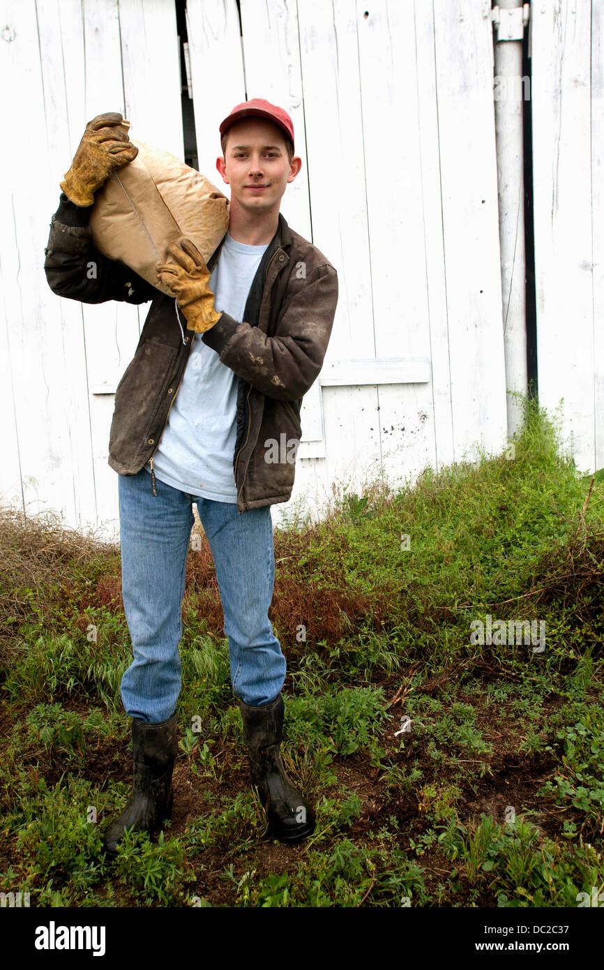 Farmer with sack of feed on shoulder - Stock Image