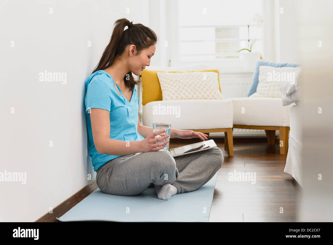 Woman sitting on mat using digital tablet Stock Photo