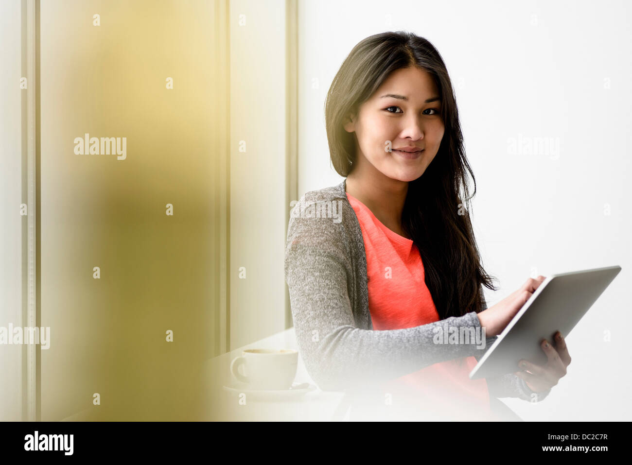 Woman looking up from digital tablet - Stock Image