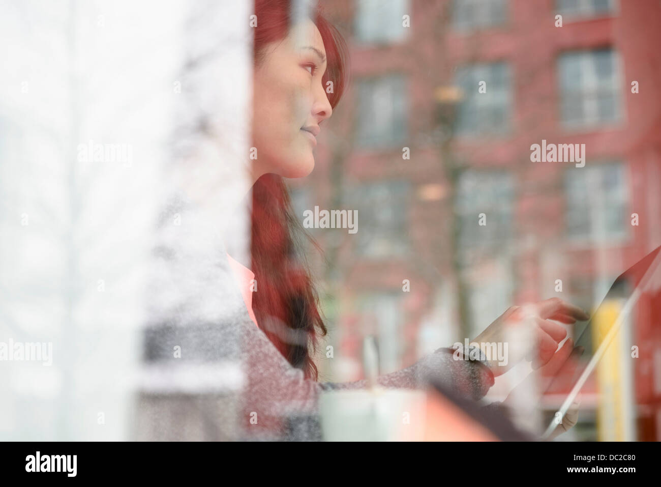 Woman with digital tablet looking out of glass window - Stock Image