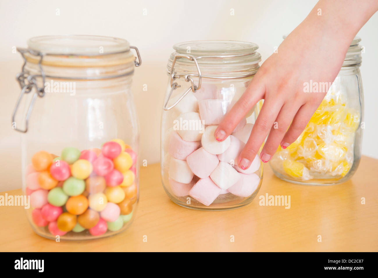 Hand touching jar of marshmallow Stock Photo