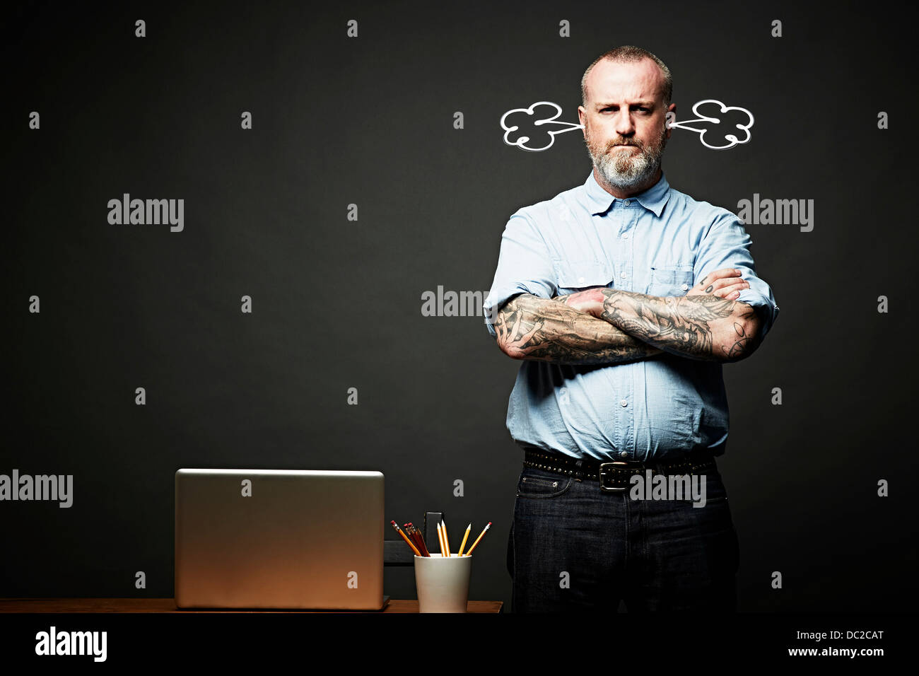 Man with arms crossed fuming in silence - Stock Image