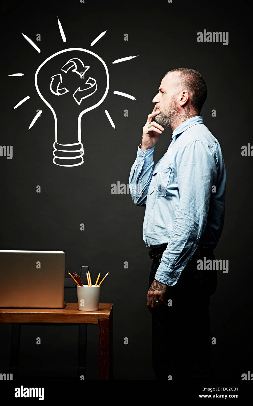 Man contemplating on recycling idea - Stock Image