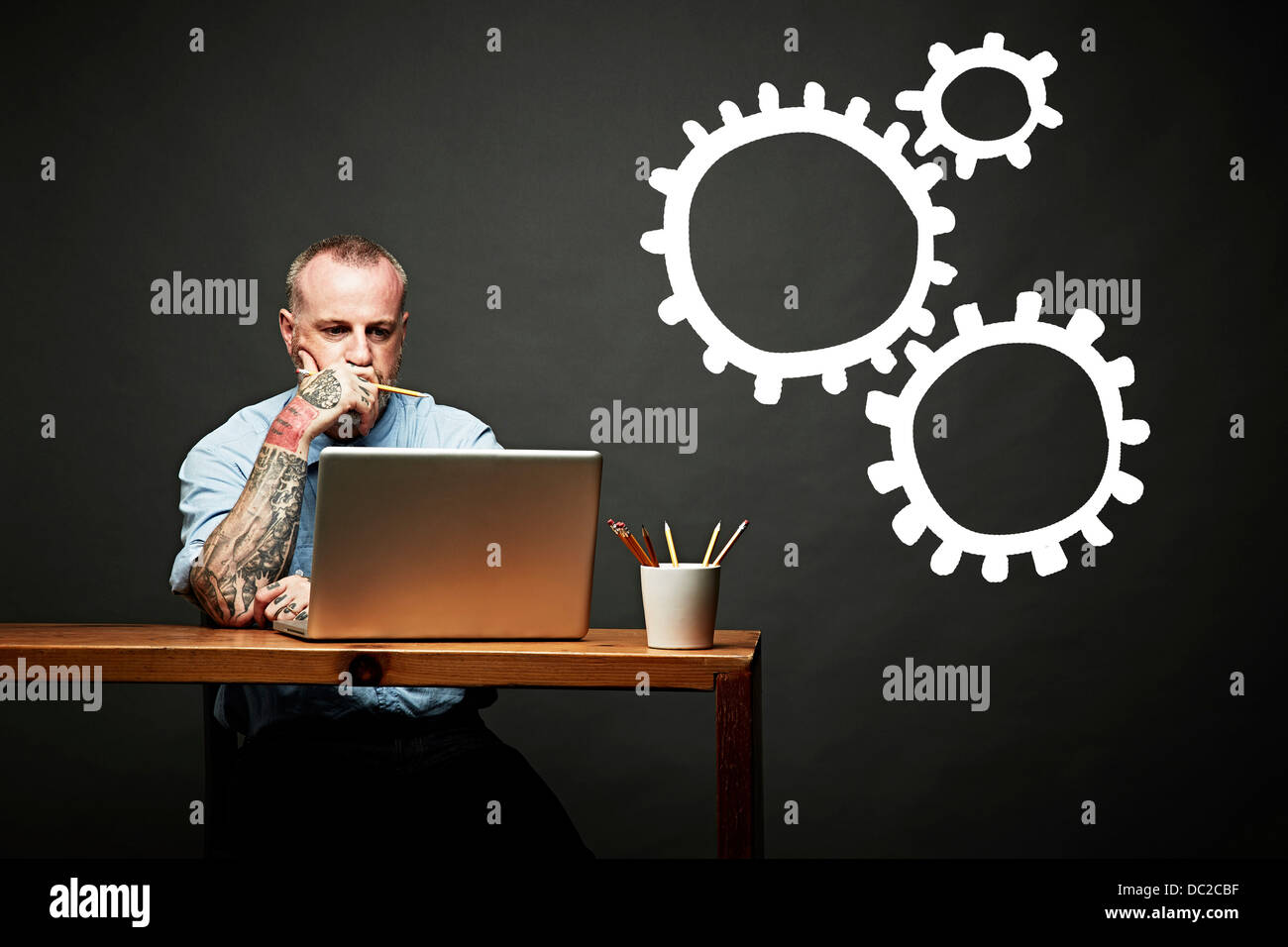 Conceptual image of man as cog in the wheel - Stock Image
