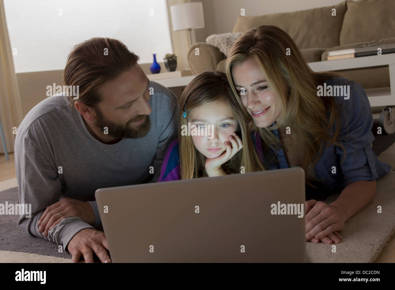 Parents and child looking at laptop - Stock Image