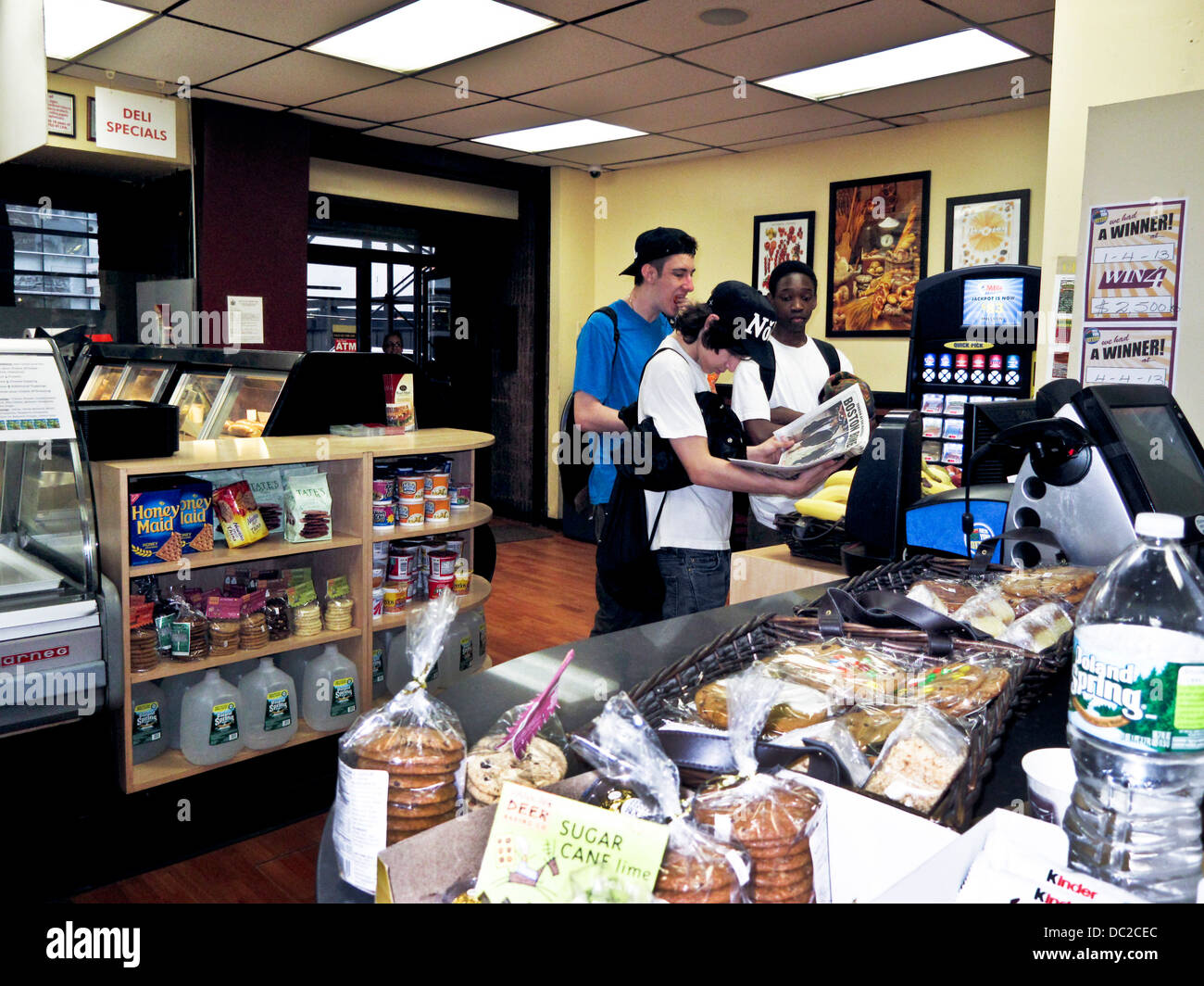3 teen boys at New York deli counter intently scanning tabloid newspaper headline for news about Boston Marathon - Stock Image