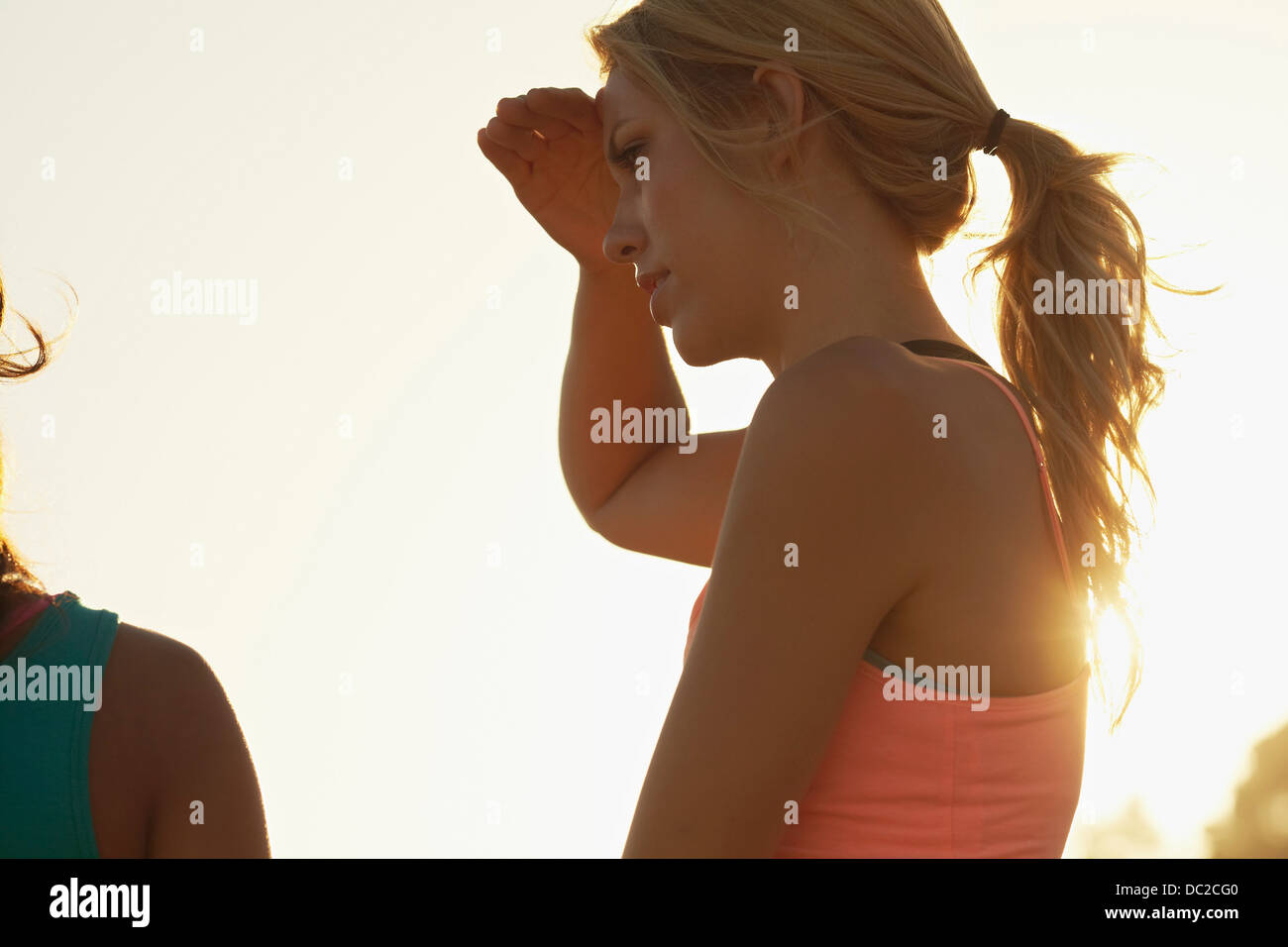 Woman blocking sun with hand Stock Photo