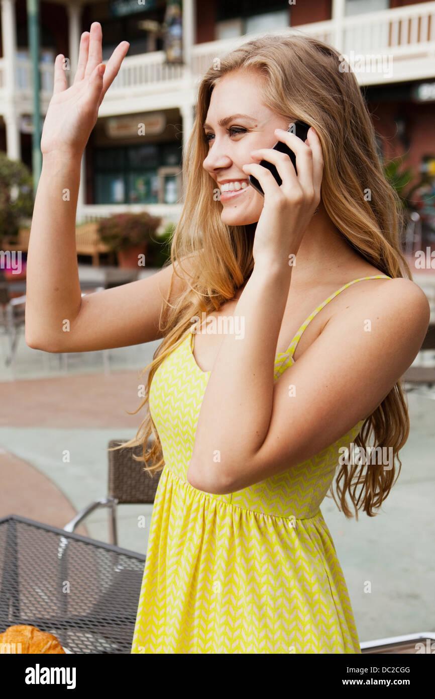 Woman on mobile phone waving - Stock Image