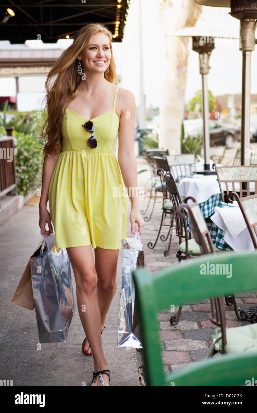 Woman shopper alongside pavement café - Stock Image