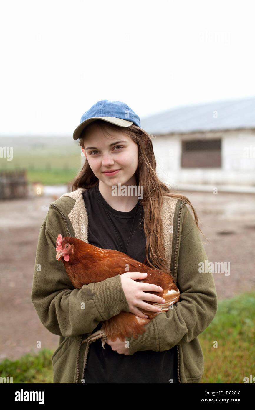 Girl carrying hen - Stock Image