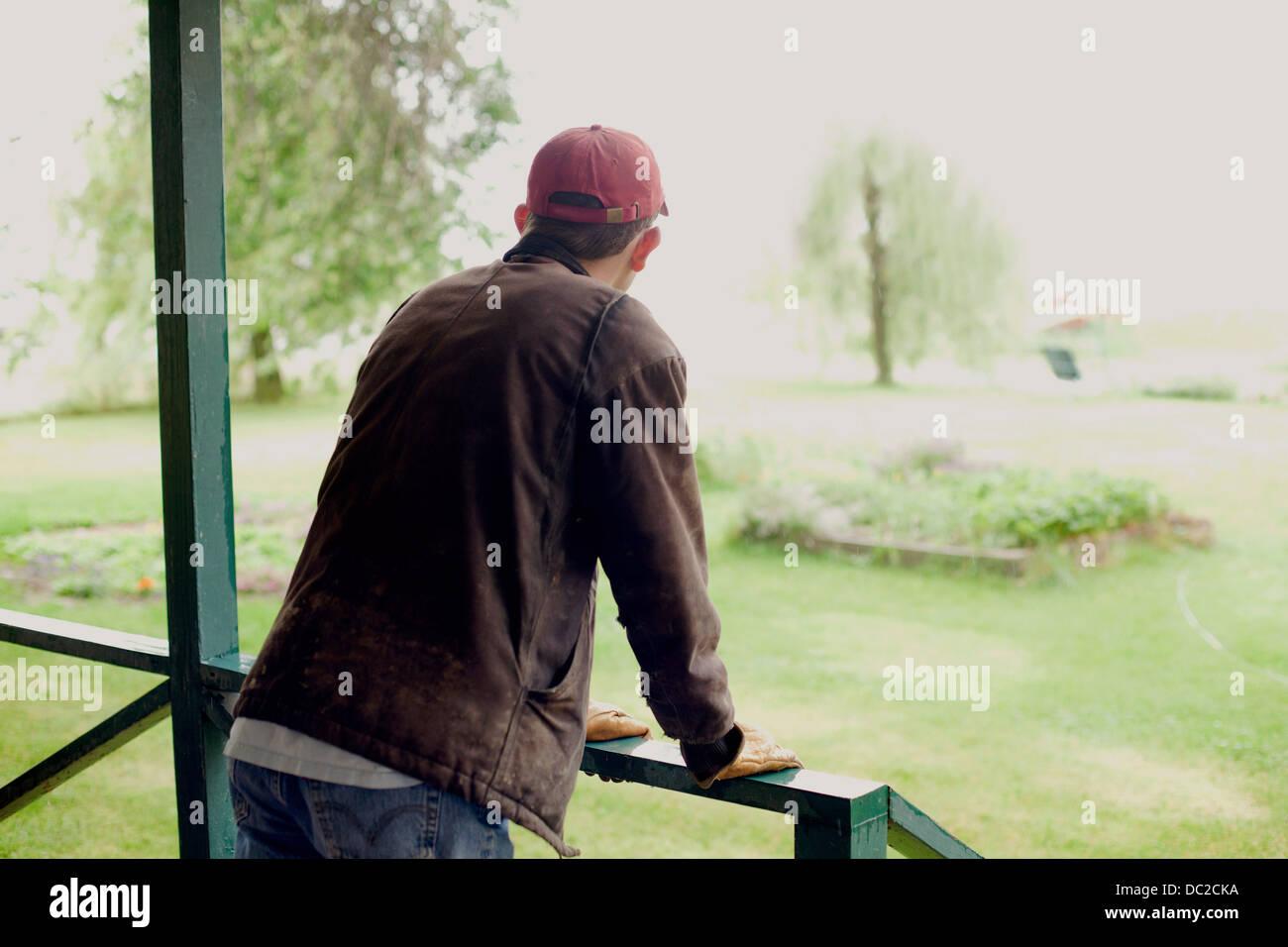 Man standing on verandah looking at garden - Stock Image
