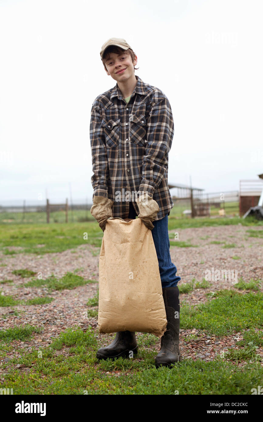 Boy carrying sack of feed - Stock Image