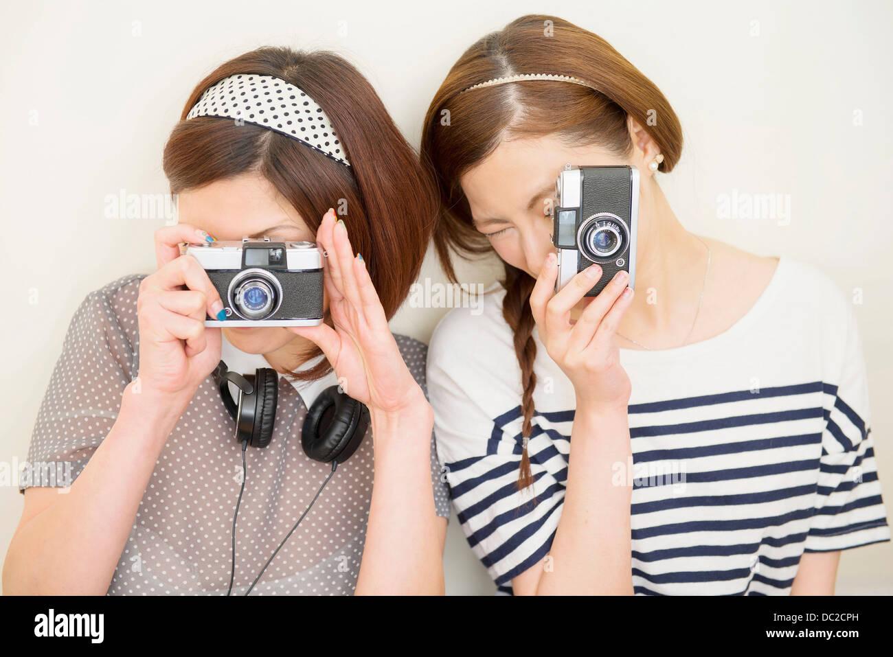 Two women taking photograph - Stock Image