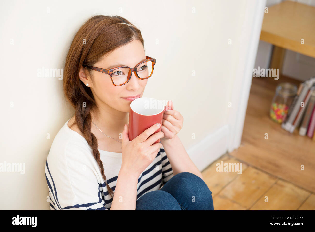 Woman day dreaming with mug of drink - Stock Image
